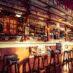 Photo of bar interior with old school clock, wooden bar stools, multi-colored alcohol bottles